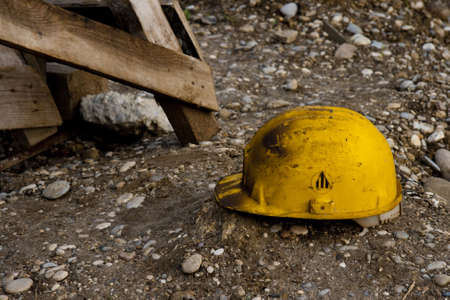 safety hat: Dirty old work helmet left on the ground of construction site