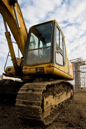 construction vibroroller: Yellow excavator on a construction site Stock Photo
