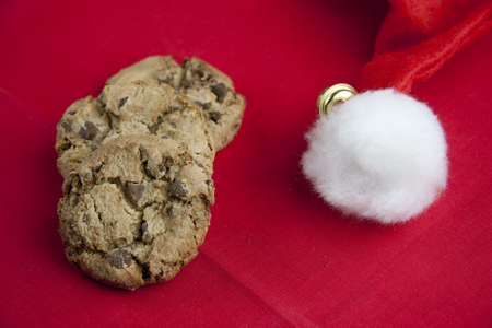 Santa hat and chocolate cookies on red table photo