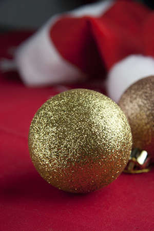Christmas balls with Santa hat on red background