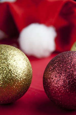 Palle di Natale con Santa cappello su sfondo rosso Archivio Fotografico