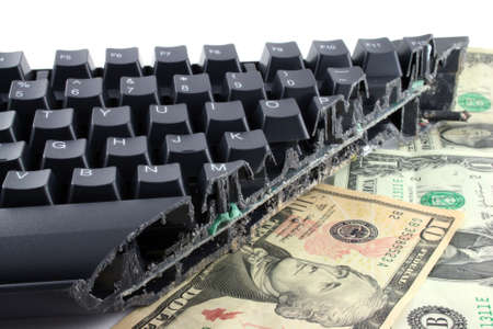 cutting costs: Modern keyboard cut completely in half showing keys and wires still in place on top of dollar notes