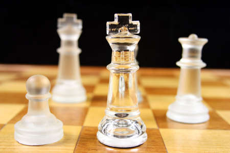 outwit: Chess Game - Glass Chess Pieces on a wooden chessboard