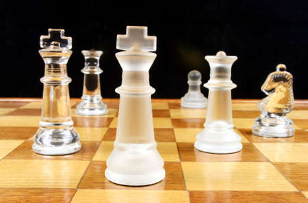 outwit: End Game - Glass Chess Pieces on a wooden chessboard   Stock Photo