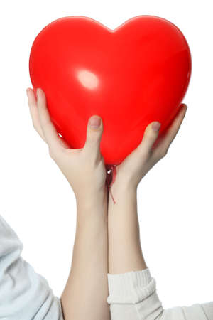 Love theme: red heart in hands of enamoured people.