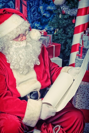 'saint nicholas': Santa Claus posing with a list of presents over Christmas background.