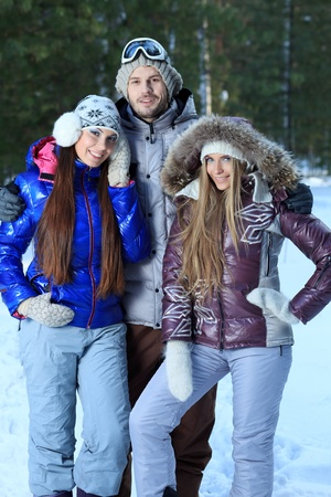Group of cheerful young people having winter rest outdoor. photo
