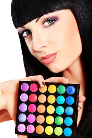 Beautiful young woman holding eye shadow palette. Isolated over white. photo