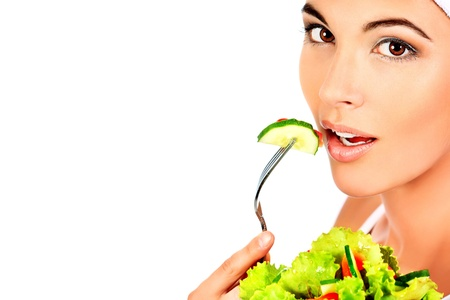 Portrait of a beautiful young woman eating vegetable salad  Isolated over white background Stock Photo - 13216278