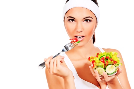 Portrait of a beautiful young woman eating vegetable salad  Isolated over white background  photo