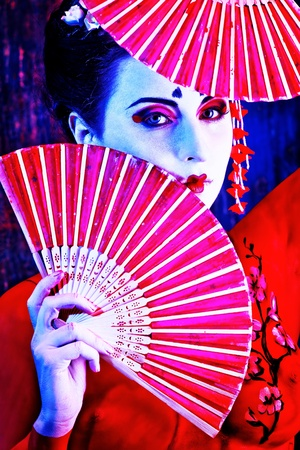 body painting: Art portrait of a stylized Japanese geisha with fan. Body painting project.