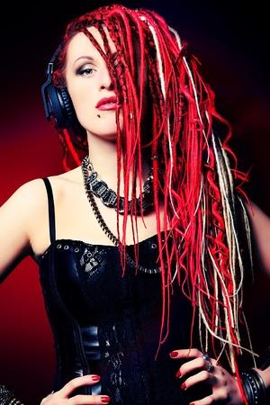 dreadlocks: Muchacha expresiva en auriculares con gran rastas rojas.