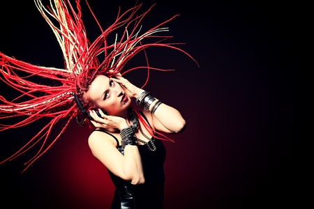 metal music: Expressive girl rock singer with great red dreadlocks. Stock Photo
