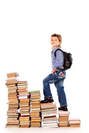 climbing stairs: Un ni�o que sube las escaleras de los libros. Educaci�n. Aislado en blanco. Foto de archivo