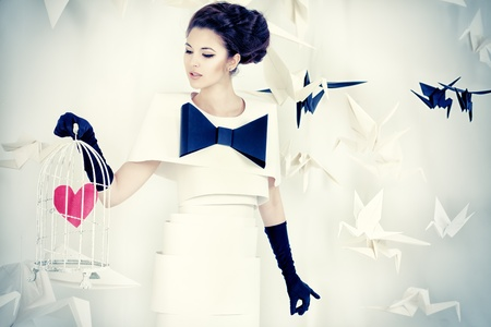 bird cage: Art fashion photo of a gorgeous woman in paper dress holding birdcage with red heart. Black and white.