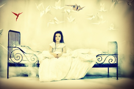 little bird: Pretty little girl sitting on her bed surrounded by paper birds. Dream world. Stock Photo