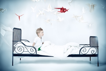 Cute little boy sitting on his bed surrounded by paper birds. Dream world. photo