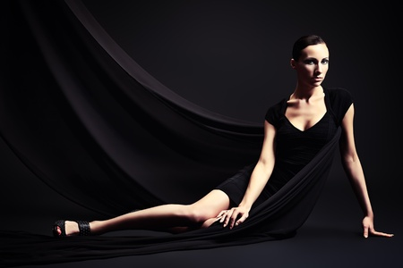 woman black background: Art fashion photo of a beautiful woman in black dress. Over black background. Stock Photo