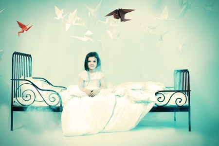 Pretty little girl sitting on her bed surrounded by paper birds. Dream world. photo