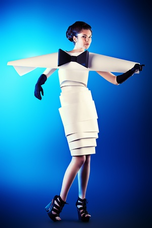 Art fashion photo of a gorgeous woman in paper dress over blue background. Black and white. photo