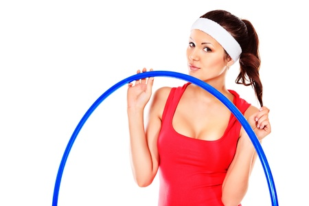 Slender young woman in sportswear making exercise with hulahoop. Isolated over white. photo