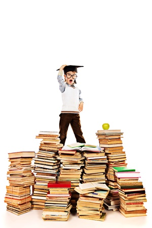 academic achievement: A boy in the academic hat standing on a pile of books. Education. Isolated over white. Stock Photo