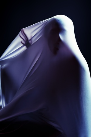 frightening: Art photo of a female silhouette breaking through the fabric. Struggle concept.