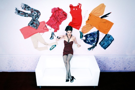 Charming fashionable woman flying in the room, surrounded by lots of her clothes  photo