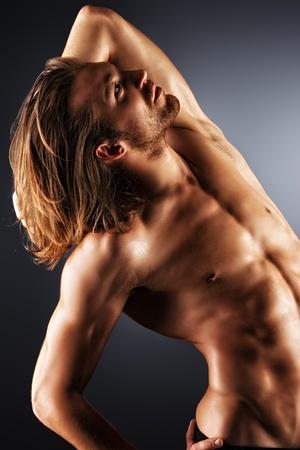 nudo maschile: Sessuale muscolare uomo posa su sfondo scuro. Archivio Fotografico