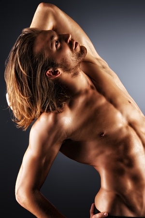 nude male: Sexual muscular man posing over dark background.