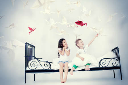 dream home: Cute kids sitting together on the bed under the blanket. Dream world. Stock Photo