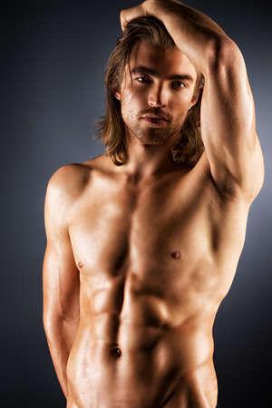 Hombre musculoso sexual que presenta sobre fondo oscuro.