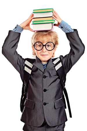 Portrait of a happy schoolboy in glasses holding a stack of books. Isolated over white background. photo