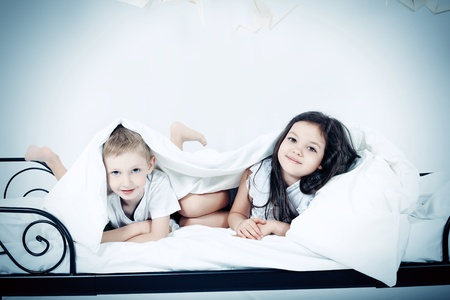 dream home: Cute kids lying together on the bed under the blanket. Dream world. Stock Photo