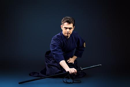 kendo: Handsome young man practicing kendo  Over dark background