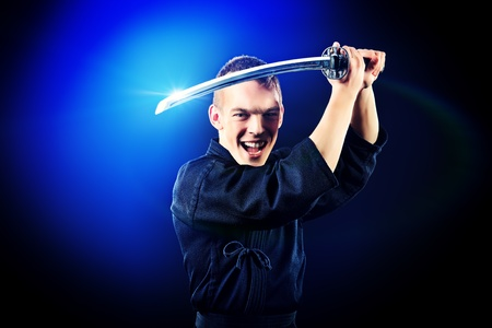 Handsome young man practicing kendo  Over dark background  photo