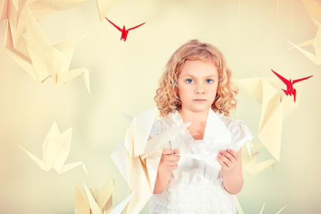 Beautiful little girl in her dream world surrounded with paper birds. photo