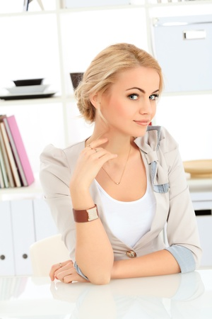 communicable: Portrait of a pretty smiling blonde woman at office. Stock Photo