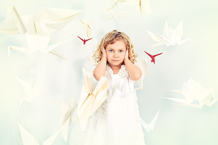 lonelyness: Beautiful little girl in her dream world surrounded with paper birds.