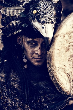 animal ritual: Portrait of a shaman with a drum outdoor.