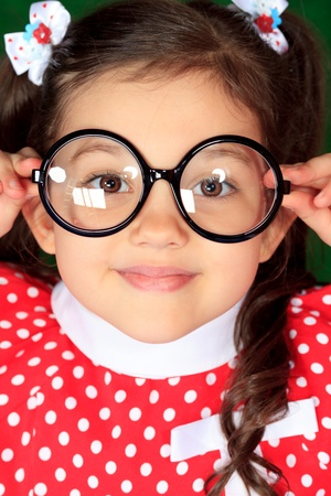 Portrait of a funny little girl in big glasses. photo