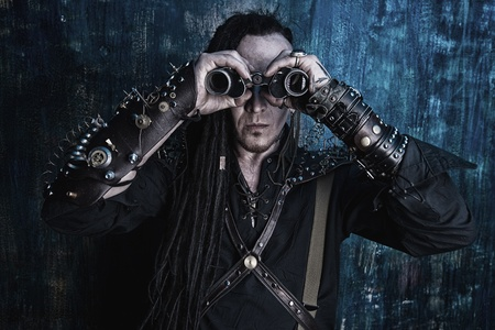 Portrait of a steampunk man looking through the binocular. Over dark grunge background. photo