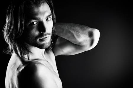 Portrait of a sexual muscular man posing over dark background.