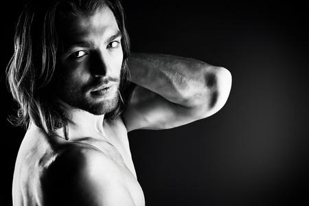 niño sin camisa: Retrato de un hombre musculoso sexual que presenta sobre fondo oscuro. Foto de archivo