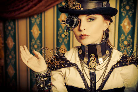 Portrait of a beautiful steampunk woman over vintage background. photo