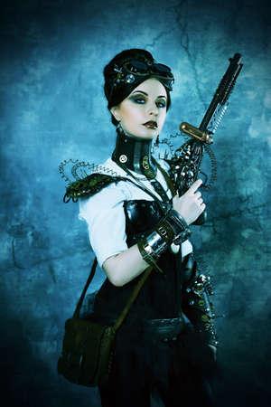 vintage gun: Portrait of a beautiful steampunk woman holding a gun over grunge background.