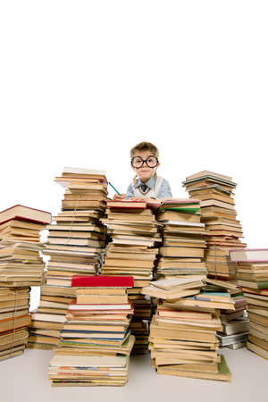 in a pile: Un ni�o sentado sobre una pila de libros y la lectura de un libro. Educaci�n. Aislado en blanco.