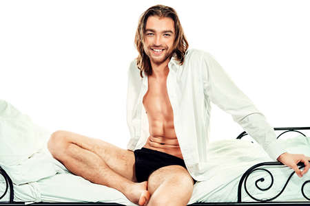 the seducer: Handsome man in an unbuttoned white shirt sitting on a bed. Isolated over white.