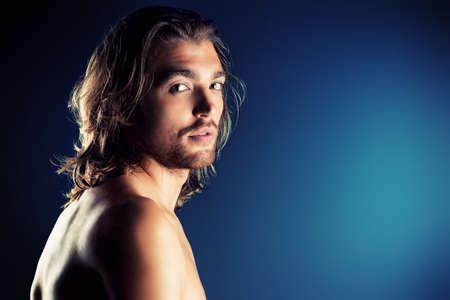 hombre sin camisa: Retrato de un hombre musculoso sexual que presenta sobre fondo oscuro. Foto de archivo
