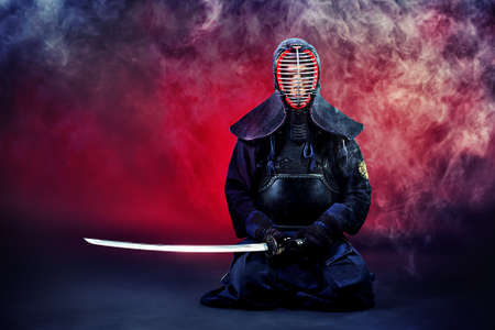 samurai: Handsome young man practicing kendo. Over dark background. Stock Photo